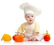 Bebê que desgasta um chapéu do cozinheiro chefe com alimento saudável imagem de stock