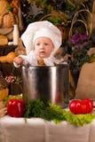 Bebê que desgasta um chapéu do cozinheiro chefe dentro de um potenciômetro conservado em estoque de cozimento Imagem de Stock
