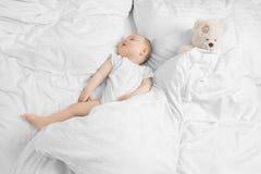 Bebê que dorme com urso de peluche Fotografia de Stock Royalty Free