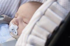 Bebê que dorme em seu carrinho de criança um o dia ensolarado fotografia de stock