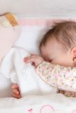 Bebê que dorme em um berço com chupeta e brinquedo Imagens de Stock