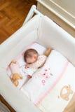 Bebê que dorme em um berço com chupeta e brinquedo Fotos de Stock Royalty Free