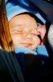 Bebê que dorme nas mãos da matriz Imagens de Stock