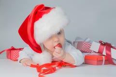 Bebê que encontra-se com presentes no chapéu de Santa no fundo cinzento Imagem de Stock
