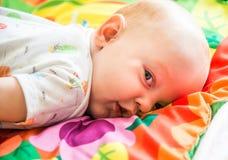 Bebê que encontra-se e que olha Foto de Stock