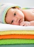 Bebê que encontra-se em toalhas coloridas Imagem de Stock Royalty Free
