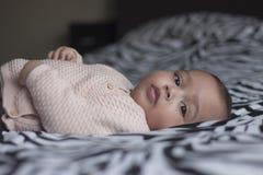 Bebê que encontra-se na cama que olha na câmera com olhos bonitos Imagem de Stock