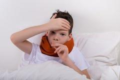 bebê que encontra-se na cama que toma a medicina para a dor de cabeça imagem de stock