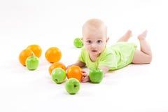 Bebê que encontra-se no fundo e que sorri entre o fruto imagem de stock royalty free