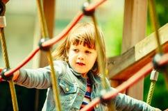 Bebê que escala em cordas no campo de jogos Imagens de Stock Royalty Free