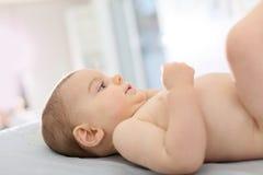 Bebê que espera um tecido novo a ser mudado foto de stock