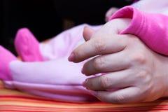 Bebê que guarda a mão da mãe fotografia de stock
