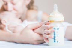 Bebê que guarda uma garrafa de bebê com leite materno Foto de Stock Royalty Free