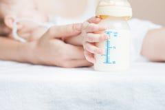 Bebê que guarda uma garrafa de bebê com leite materno Fotografia de Stock Royalty Free
