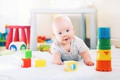 Bebê que joga com brinquedos coloridos em casa fotos de stock