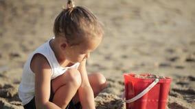 Bebê que joga com a cubeta e a pá vermelhas do brinquedo no Sandy Beach vídeos de arquivo