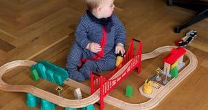 Bebê que joga com estrada de ferro de madeira