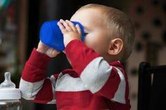 Bebê que joga com a garrafa e a caneca internas Imagens de Stock