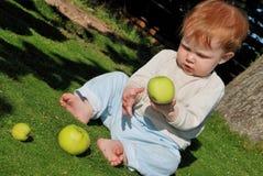 Bebê que joga com maçãs Imagens de Stock Royalty Free