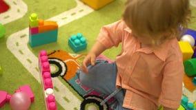 Bebê que joga com multi blocos de apartamentos coloridos no jardim de infância Desenvolvimento infantil no infantário filme