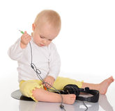 Bebê que joga com os auscultadores no fundo branco Imagem de Stock Royalty Free