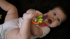 Bebê que joga com os brinquedos coloridos no fundo escuro