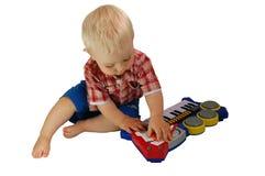 Bebê que joga com piano dos brinquedos Fotografia de Stock