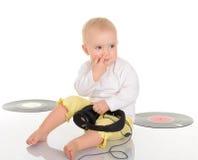 Bebê que joga com registro de vinil e os auscultadores velhos Imagem de Stock