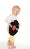 Bebê que joga com registro de vinil velho no fundo branco Imagens de Stock Royalty Free