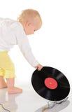 Bebê que joga com registro de vinil velho no fundo branco Imagem de Stock