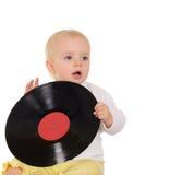 Bebê que joga com registro de vinil velho no fundo branco Fotografia de Stock