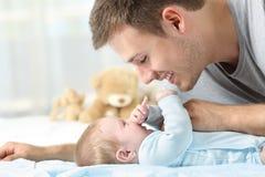 Bebê que joga com seu pai imagens de stock