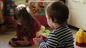 Bebê que joga com sua irmã no berçário video estoque