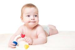 Bebê que joga com um chocalho Fotografia de Stock Royalty Free