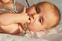 Bebê que joga com um estetoscópio Fotografia de Stock Royalty Free