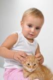 Bebê que joga com um gatinho Imagens de Stock