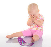 Bebê que joga com uma imagem no fundo branco Foto de Stock