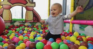 Bebê que joga na associação colorida da bola do campo de jogos video estoque