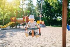 Bebê que joga no campo de jogos que tem o divertimento Fotos de Stock Royalty Free