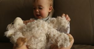 Bebê que joga o brinquedo macio no sofá filme