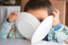 Bebê que joga o esconde-esconde com prato 2 Imagem de Stock Royalty Free