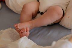 Bebê que mantém os pés cruzados Fotografia de Stock