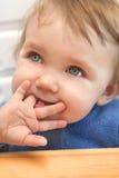 Bebê que mastiga em um dedo Fotografia de Stock Royalty Free