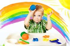 Bebê que modela a argila colorida, bolas da massa da cor da criança, arte da criança foto de stock royalty free
