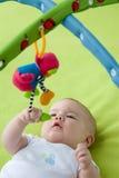 Bebê que olha acima em um brinquedo móvel fotografia de stock royalty free
