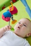 Bebê que olha acima em um brinquedo móvel Imagens de Stock Royalty Free