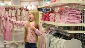 Bebê que olha a roupa na loja elegante video estoque