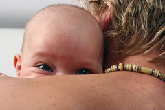 Bebê que presta atenção sobre o ombro Fotos de Stock Royalty Free