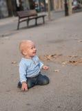Bebê que rasteja na rua e no sorriso Fotografia de Stock