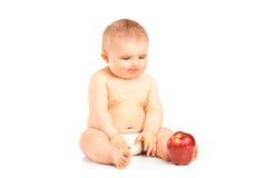 Bebê que senta e que olha uma maçã Foto de Stock Royalty Free